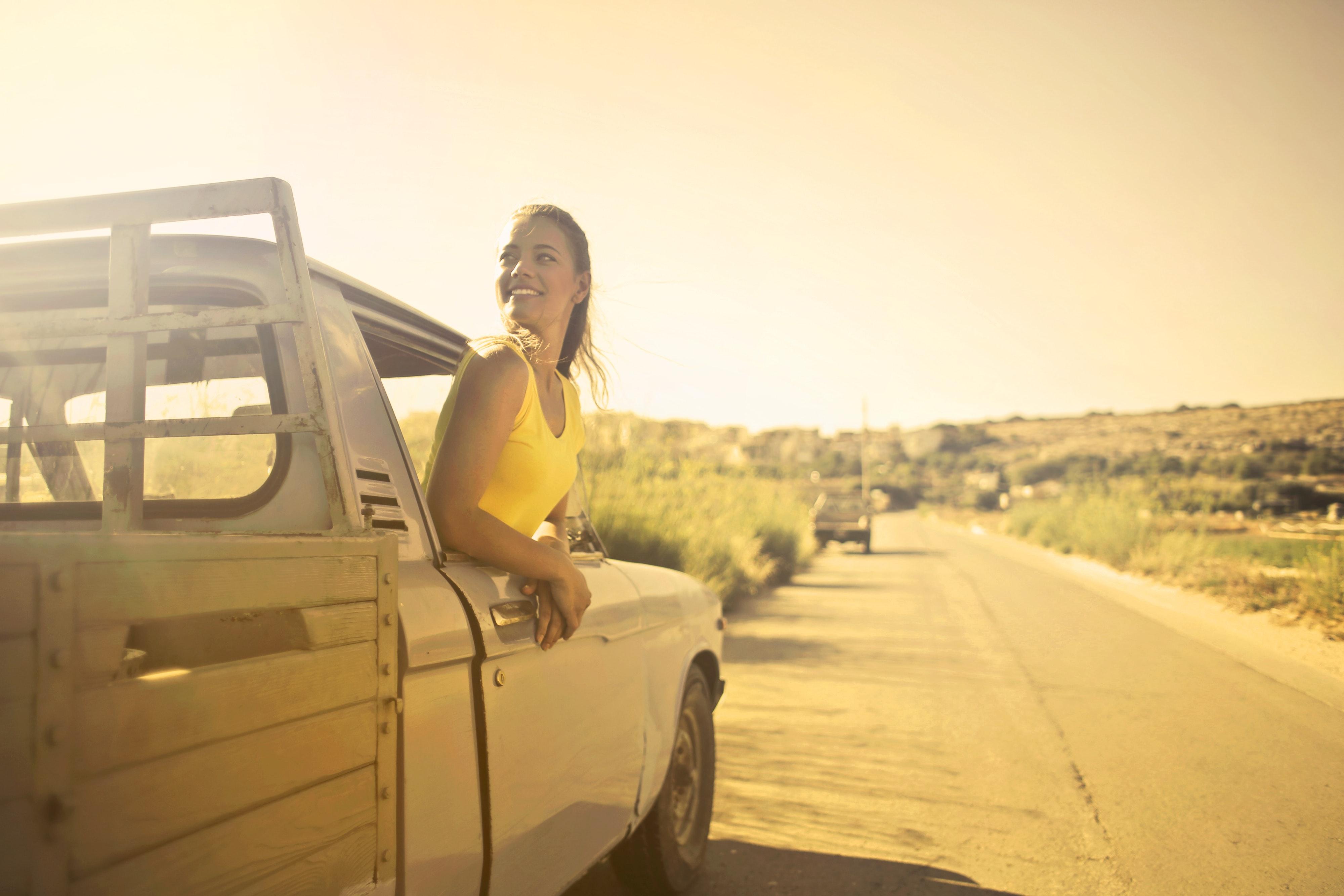 Photo d'une fille en voiture, sortant la tête par la fenêtre pour admirer la route !
