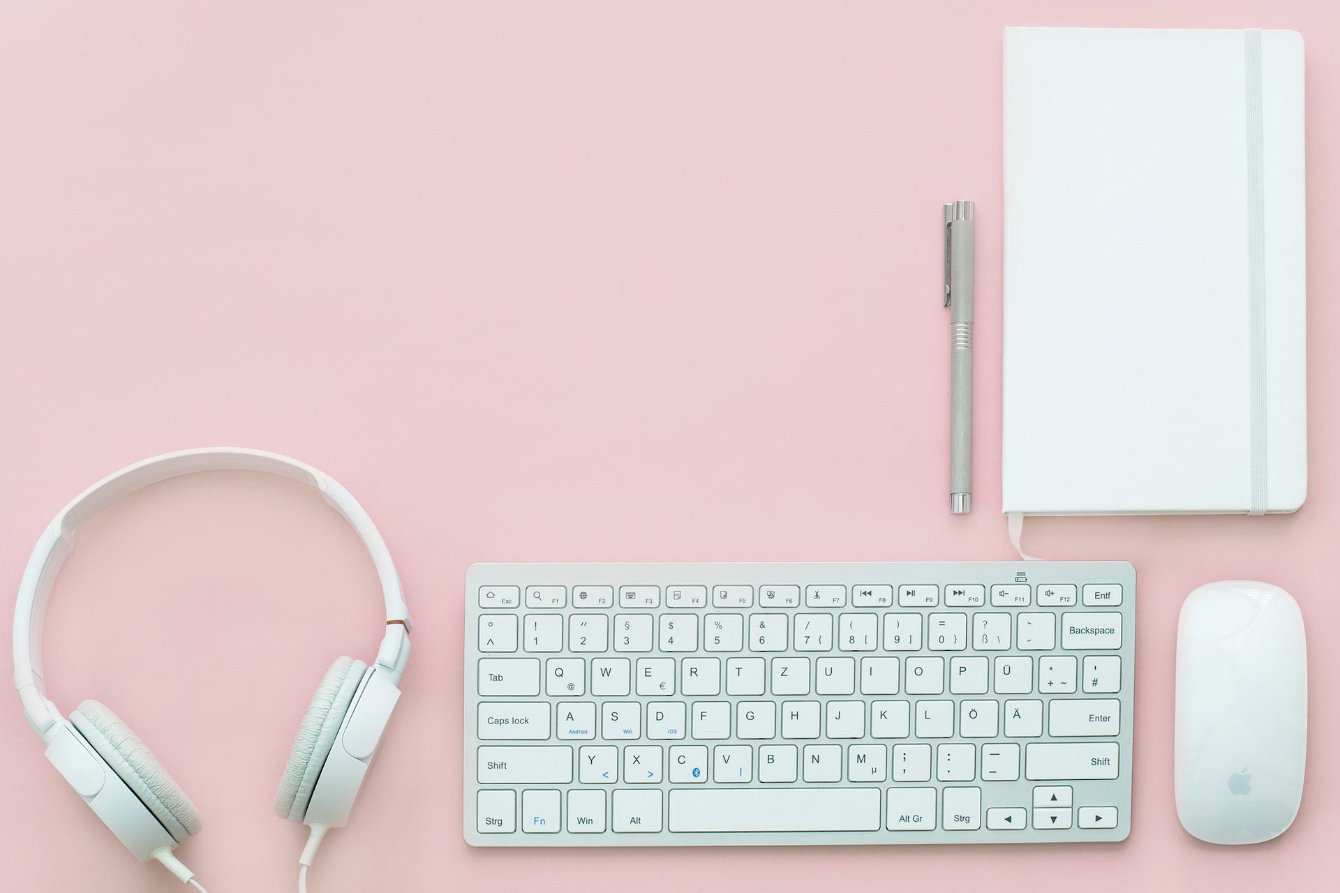 Une photo prise de haut d'un bureau rose avec un casque, un clavier, une souris, un bloc-note. Le tout est blanc.